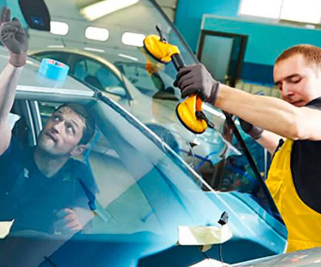 miehet vaihtamassa auton tuulilasia